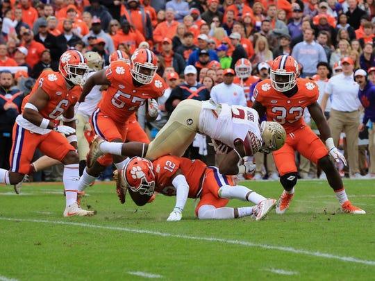 Florida State freshman running back Cam Akers hurls himself over Clemson sophomore defensive back K'von Wallance during the 2nd quarter.