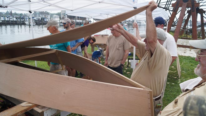 Mel Fortney (right) describes how to fit and secure a plywood bottom to a skiff's hull during Family Boat Building Weekend in Lewes on Saturday. The Lewes Historical Society's volunteers coached families for three days as they built seaworthy, 12-foot skiffs.