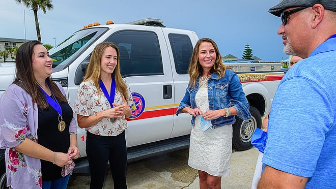 Kelsey Genners, Leanna Swilley, Kelly Cox and Rod Boothe talk outside of the St. Johns County beach rescue office in St. Augustine Beach on Tuesday after a ceremony honoring Boothe, Genners and Swilley for saving Cox's life after she was caught in a rip current in May.