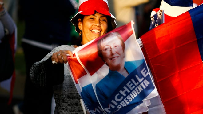A supporter of Chile's former President Michelle Bachelet celebrates partial election results in Santiago, Chile, Sunday.