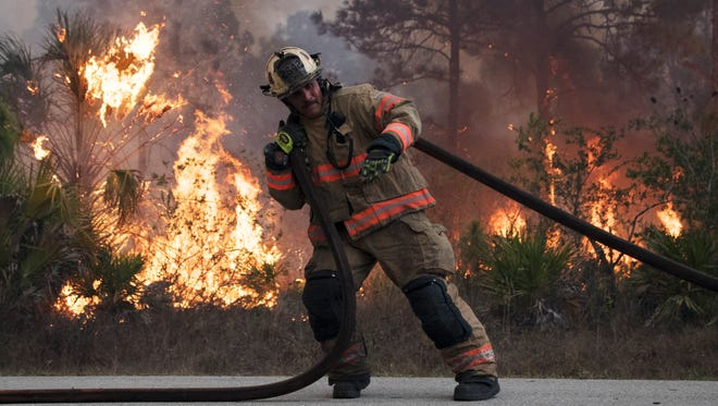 A firefighter with the Fort Myers Fire Department works a major fire that erupted in Lehigh Acres on April 21.