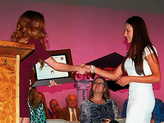 Courtesy Photo   Nadine Ramirez, right, accepts her Rachel Herrera Memorial Scholarship during Monday's Deming High School Senior Scholarship Awards Night at the Deming Public Schools Auditorium. Ramirez was named to the New Mexico State University Regents Success Scholarship spread over four yearsw at 26,916. She also was named recipient of three local scholarships; Luna County Employee Charity (400), Deming Masonic Lodge 12 (1,000) and the Herrera award (4,000).
