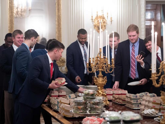 TOPSHOT - Guests select fast food that the US president purchased for a ceremony honoring the 2018 College Football Playoff National Champion Clemson Tigers in the State Dining Room of the White House in Washington, DC, January 14, 2019. - US President Donald Trump says the White House chefs are furloughed due to the partial government shutdown. (Photo by SAUL LOEB / AFP)SAUL LOEB/AFP/Getty Images ORIG FILE ID: AFP_1C87MJ