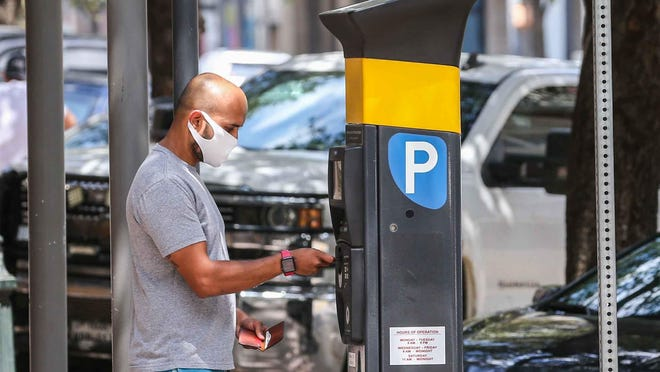Sujan Patel pays for a parking spot on Congress Avenue and Seventh Street in downtown Austin on Monday. A new payment system for parking on the street in Austin will eliminate the need to display a sticker on their vehicles, the Austin Transportation Department said.