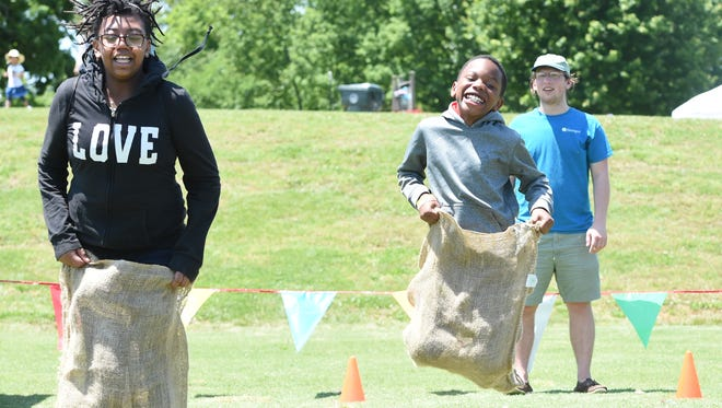 Siblings Brittany Page, 11, and Deon Page, 9, from left, compete in a sack race during Let's Move! at Victor Ashe Park on Saturday, May 7, 2016. The event, promoting healthy eating and outdoor play, is part of a national campaign to fight childhood obesity initiated by First Lady Michelle Obama. (ADAM LAU/NEWS SENTINEL)