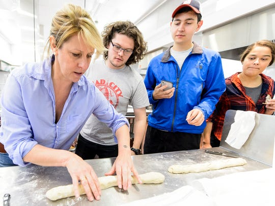 Michelle Clasen (left), of Clasen's Bakery, demonstrates how to roll bread dough to students during a Fermented Food and Beverage class. The students in the course are helping to test the strains of yeast for suitability in bread baking, and are partnering with Clasen's Bakery in Middleton, Wisconsin to do so.