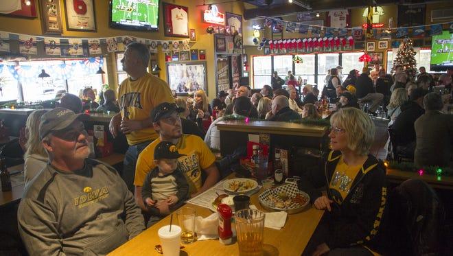 John Donovan, left, watches the TaxSlayer Bowl with Ryan Burr, 15-month-old Jax Burr and Joy Burr at the Coach's Corner on Friday, Jan. 2, 2014. David Scrivner / Iowa City Press-Citizen
