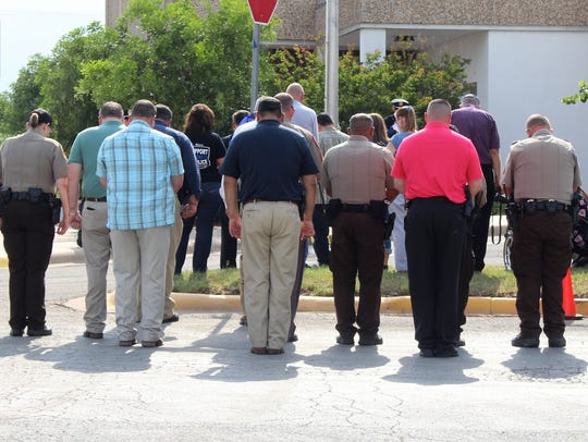 Officers and community members bow their heads during