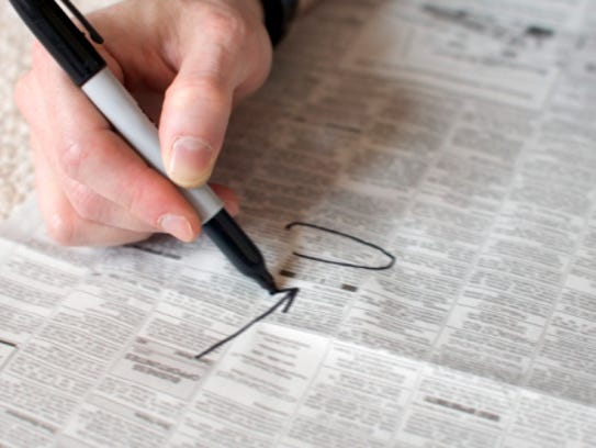 A stock image of a person circling ads in a newspaper.
