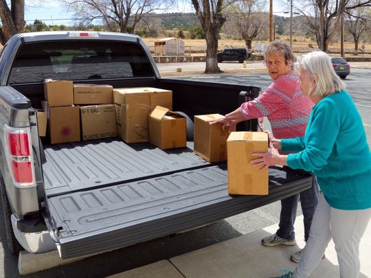 Volunteers with Fort Stanton Inc. pack up merchandise from the fort's gift shop.