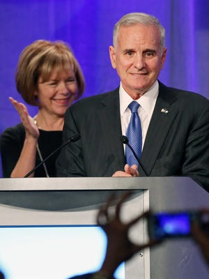 Democratic Gov. Mark Dayton receives applause as he addresses supporters after winning his gubernatorial race against Republican Jeff Johnson, on Tuesday, in Minneapolis. At left is his running mate, Tina Smith.