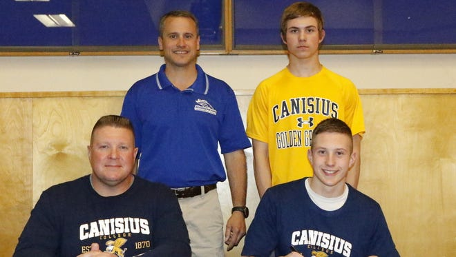 Kenyon Winkky signs a ceremonial Letter of Intent on Tuesday at Horseheads High School to swim at Division I Canisius College. Next to him is his dad, Eric Winkky. In the back, from left, are Horseheads boys swimming coach Jared Zembek and Kaelan Winkky, who is Kenyon's brother.