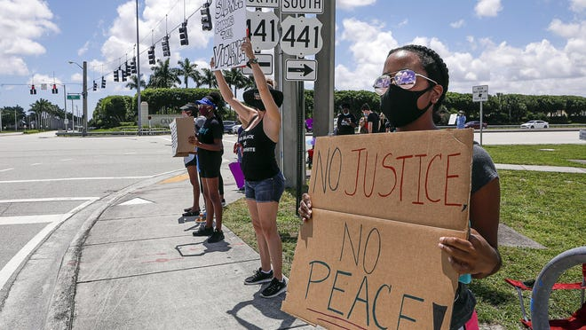 Wellington resident Maya Rose takes part in a peaceful Black Lives Matter rally at the intersection of 441 and Forest Hill Blvd. on June 13.