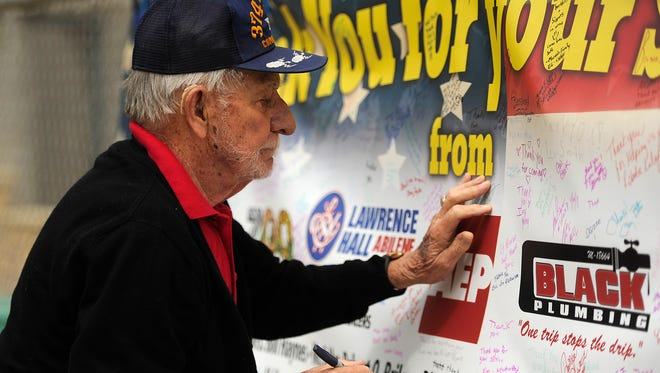 Retired U.S. Air Force Colonel Jim Alexander signs a banner thanking the troops for their service during the Zoolute on Saturday, May 20, 2017, at the Abilene Zoo.
