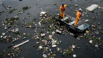 "Workers gather debris carried by the tide and caught by the ""eco-barrier"" before entering Guanabara Bay July 20."