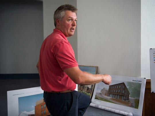Developer Thomas Krajewski shows renderings at the site of the future commercial mixed-use Baker Creek Bottoms in South Knoxville Wednesday, June 6, 2018. Plans for the vendor filled space include food, drink, bike rental and repair, and a large event space.