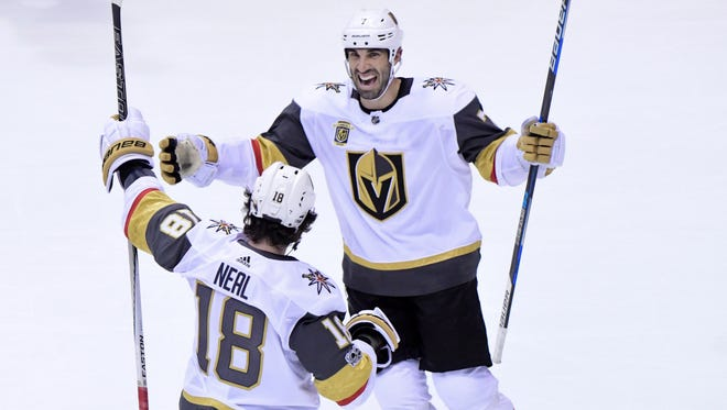 Vegas Golden Knights left wing James Neal (18) celebrates with defenseman Jason Garrison (7) after scoring the game-winning goal in overtime against the Arizona Coyotes.
