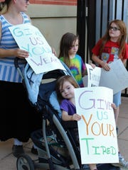 Amy Blackbear, left, brought her three children - Mistaya, 3, in the stroller, Robert, 6, center and Joseph, 8 - to Saturday evening's family rally at Everman Park.
