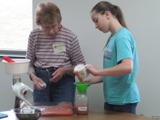 Ally fills her jar with applesauce during Caroline's Food Preservation session.