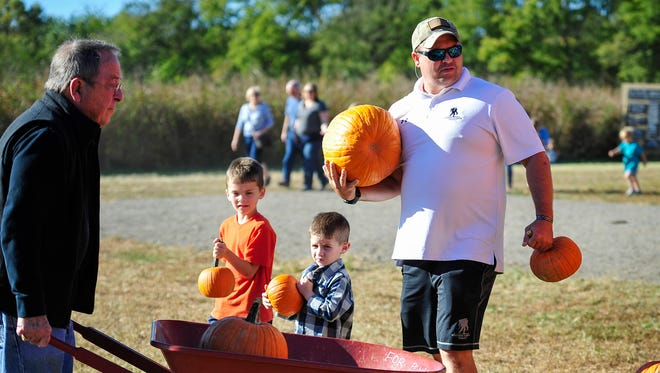 Jonathan Thomas, right and his son Johnny, 4, center, and his cousin Daniel Davenport, 6, carry their pumpkins to the car at Gentry's Farm, Saturday, October 8, 2016, in Franklin.