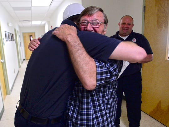 Truck driver Paul Bristol embraces Williston Firefighter