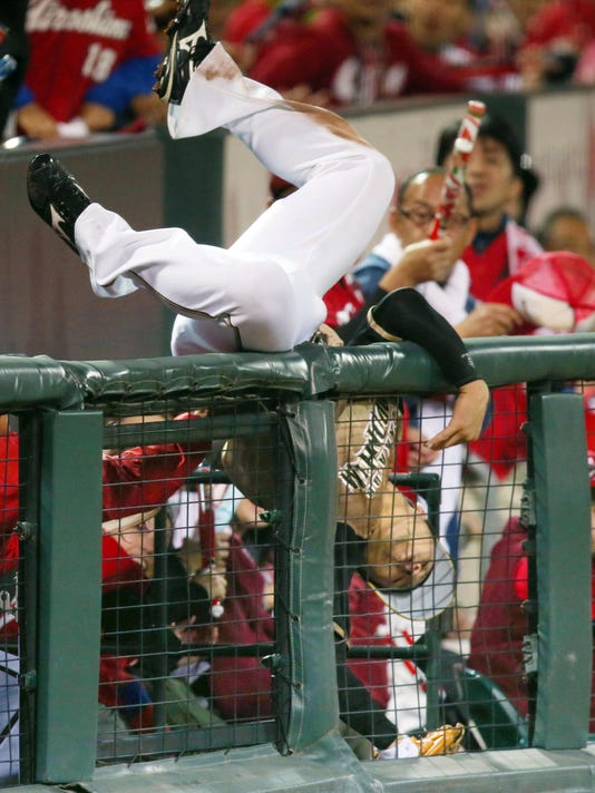 Nippon Ham Fighters' Kensuke Kondo dives into a stand in attempt to catch a fly ball hit by Hiroshima Carp's Brad Eldred during the fifth inning of Game 6 of baseball's Japan Series at Mazda stadium in Hiroshima, Hiroshima prefecture, western Japan Saturday, Oct. 29, 2016. (Takahiko Kanbara/Kyodo News via AP)