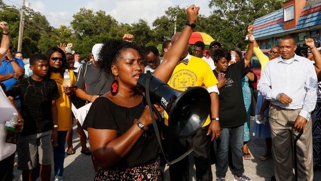 In this Sunday, July 22, 2018 photo, Ruth Beltran, of Black Lives Matter Tampa, speaks to the crowd about standing up for the rights of black people in the community as family, friends and demonstrators gather in a parking lot in Clearwater, Fla.