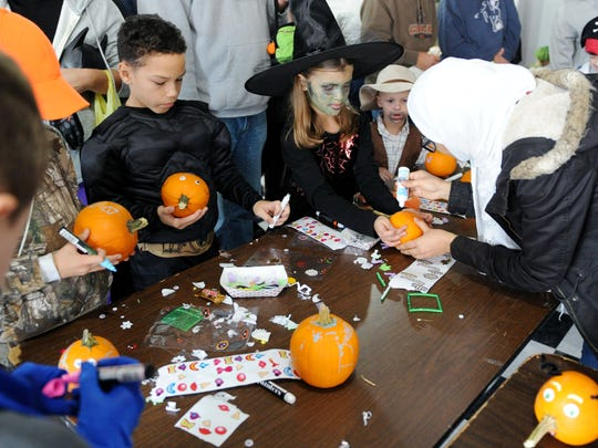 Kids decorate pumpkins during Halloween on Franklin Street during last year's Halloween event.