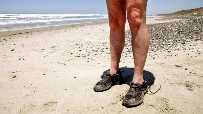 A man strolls along another nude beach in California wearing nothing but running shoes.