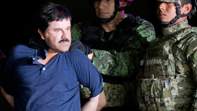 "In this Jan. 8, 2016 photo, a handcuffed Joaquin ""El Chapo"" Guzman is made to face the press as he is escorted to a helicopter by Mexican soldiers and marines at a federal hangar in Mexico City. Guzman is scheduled to appear in person in a federal court in New York. A judge initially ruled that Guzman would appear in court by video on Friday, Feb. 3, rather than have marshals escort him to and from a high-security Manhattan jail cell. The order was changed after his lawyers asked the judge to reconsider."