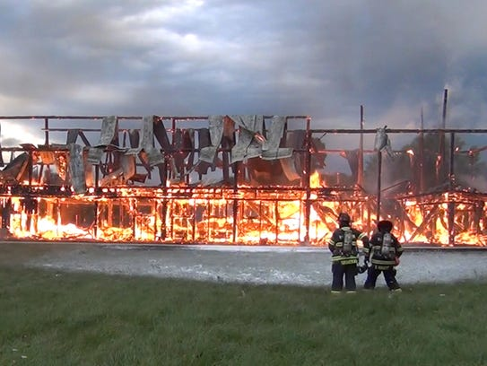 Fire crews spray foam at what is left of the old dairy