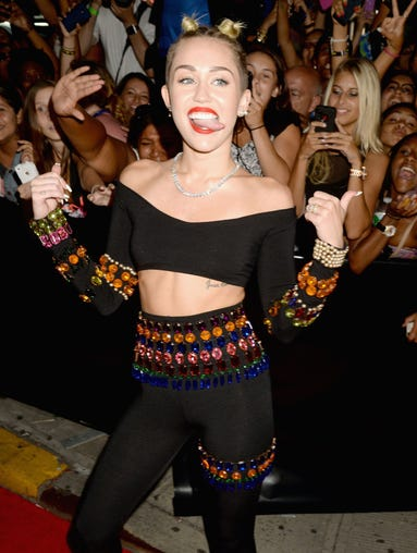A photo of Miley Cyrus on the red carpet must show some tongue and some tummy, right?
