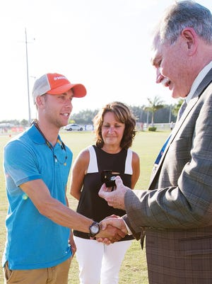 Adam Sommer, left, and Susan Sommer, center, accept the Florida High School Athletic Association Honor of Distinction award, a ring, on behalf of the late Jeff Sommer on Thursday from FHSAA executive director Roger Dearing at Estero High School. Susan is Jeff Sommer's wife and Adam is their son.