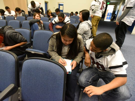 Tsé Bit'a'í Middle School eighth grader Shanti Begay, left, gets help on a math assignment from Adrian Gibson, a Shiprock High School junior and wide receiver for the football team, on Thursday at the middle school in Shiprock.