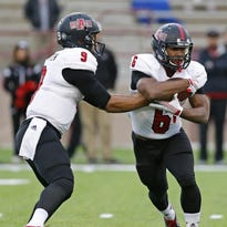 Arkansas State quarterback Fredi Knighten (9) hands the ball to running back Warren Wand during the second half against New Mexico State in Las Cruces, N.M., on Saturday. Arkansas State won 52-28.
