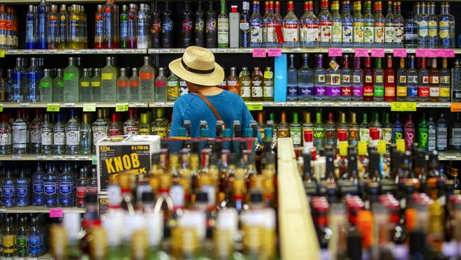 A customer at South Eugene Liquor Store peruses the vodka selections.  [Andy Nelson/The Register-Guard] - registerguard.com