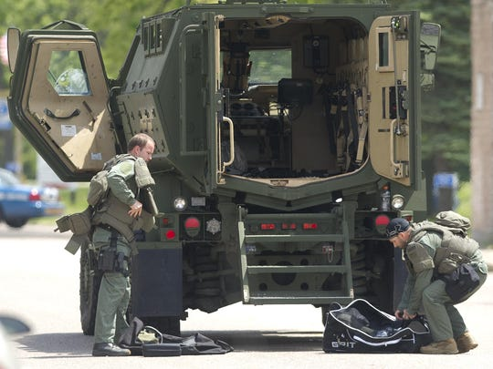 Officers change into tactical gear near the Portage County Sheriff's Office's armored vehicle during a standoff in Bancroft, Wednesday, June 3, 2015.
