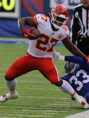 Kansas City Chiefs running back Kareem Hunt is grabbed by New York Giants free safety Andrew Adams as he runs he caught a screen pass in the first half.