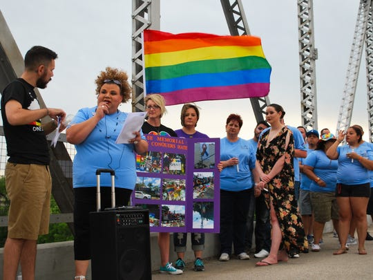 K'Danz Cruz, Director of LGBT+ Services at Open Arms welcomes attendees to the candlelight vigil at Lone Wolf Bridge (06/12/17).