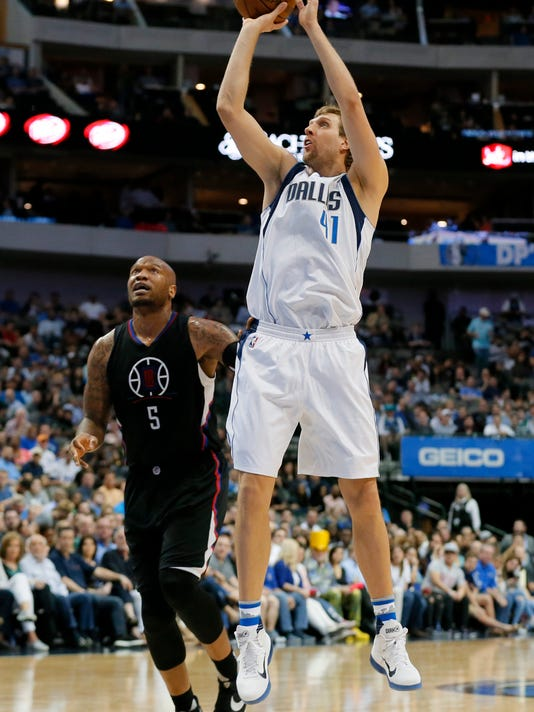 Dallas Mavericks forward Dirk Nowitzki, of Germany, attempts a shot after getting past Los Angeles Clippers' Marreese Speights (5) in the second half of an NBA basketball game in Dallas, Thursday, March 23, 2017. (AP Photo/Tony Gutierrez)