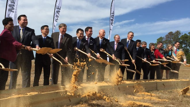 Government and economic development officials, including Gov. Rick Scott (seventh from the left), pose during the ceremonial groundbreaking at VT Mobile Aerospace Engineering Inc.'s facility site at Pensacola International Airport.