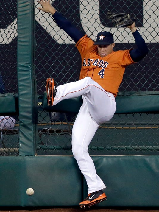 Houston Astros right fielder George Springer (4) misses the catch against the bullpen fence, giving Seattle Mariners' Kyle Seager a two-run double, in the sixth inning of a baseball game on Friday, May 2, 2014, in Houston. (AP Photo/Pat Sullivan)