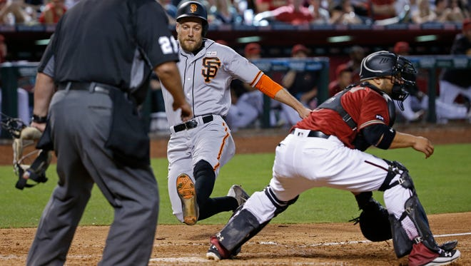 Hunter Pence of the Giants scores past Diamondbacks' catcher Wellington Castillo in the ninth inning at Chase Field on May 15, 2016 in Phoenix, Ariz.
