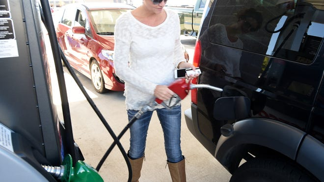 A customer pumps up gas at the Costco Wholesale gas station in this file photo.
