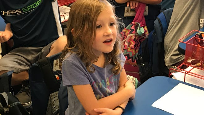 Olivia McIlwain, 7, listens intently as Tracy Kirk Crump discuss the story she wrote about the relationship between Crump's late father and children at Lewisburg Primary School.