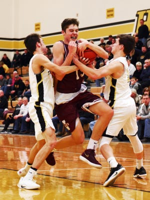 Newark's J.T. Shumate is sandwiched by Tri-Valley's Garrett Lapp, left, and Matt King during the second half of the Wildcats' 54-41 win on Wednesday night. Shumate scored a game-high 22 points with four 3-pointers.