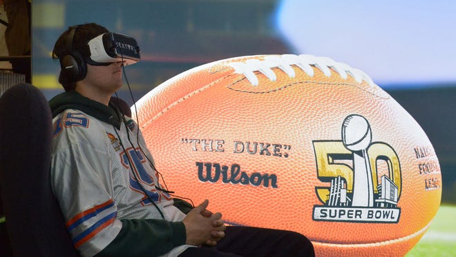 Feb 3, 2016: A fan wears goggles and headphones at the virtual reality exhibit at the NFL Experience at the Moscone Center.