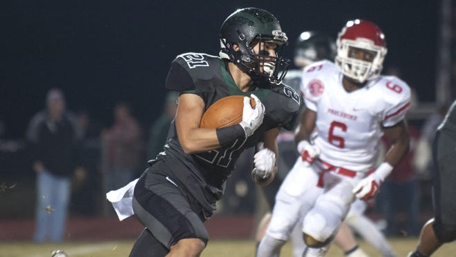 West Deptford running back Kenny Lim runs past Paulsboro's Bryce Holloway during the first quarter of Friday's game.