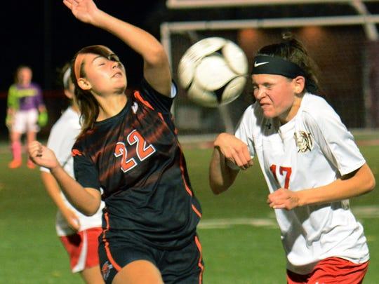 Susquehannock's Mia Dills heads the ball with Northeastern's