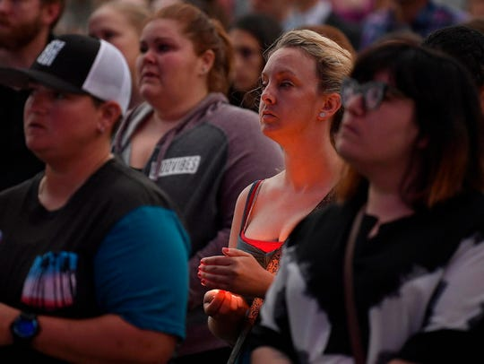 Crowd members hold candles in memory of the Las Vegas